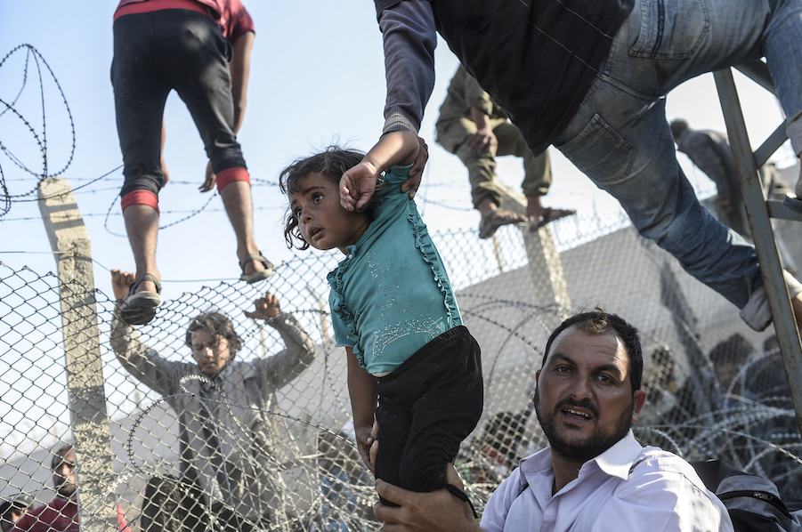 Syrian refugees cross into Turkey through a broken fence near the official border crossing at Akçakale on June 14, 2015.