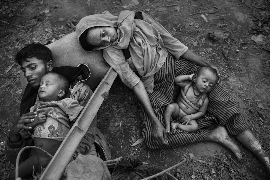 On October 2, 2017, Minara Hassan and her husband, Ekramul, lie exhausted on the ground with their children on the Bangladesh side of the Naf River, after fleeing their home in Maungdaw, Myanmar.