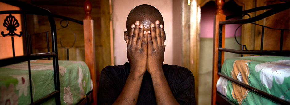 A boy covers his face after going through a trafficking ordeal. He waits to be reunited with his family at a safe place.