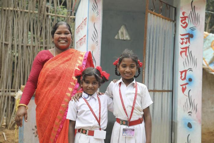 Alka Minj stands with her daughters outside a toilet she built in Jharkhand, India. She is paying for her daughters' education using her income as a mason.