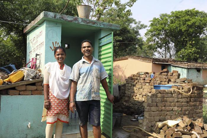 Raimuni, 28, stands with her husband outside the toilet she built in their home as part of a UNICEF sanitation program in Jharkhand, India.