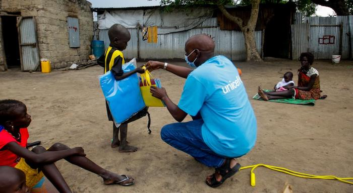 Bachuy Kier, who runs the UNICEF child protection programs in Pibor, South Sudan, hands a reintegration kit to a child who is about to be reunited with family.