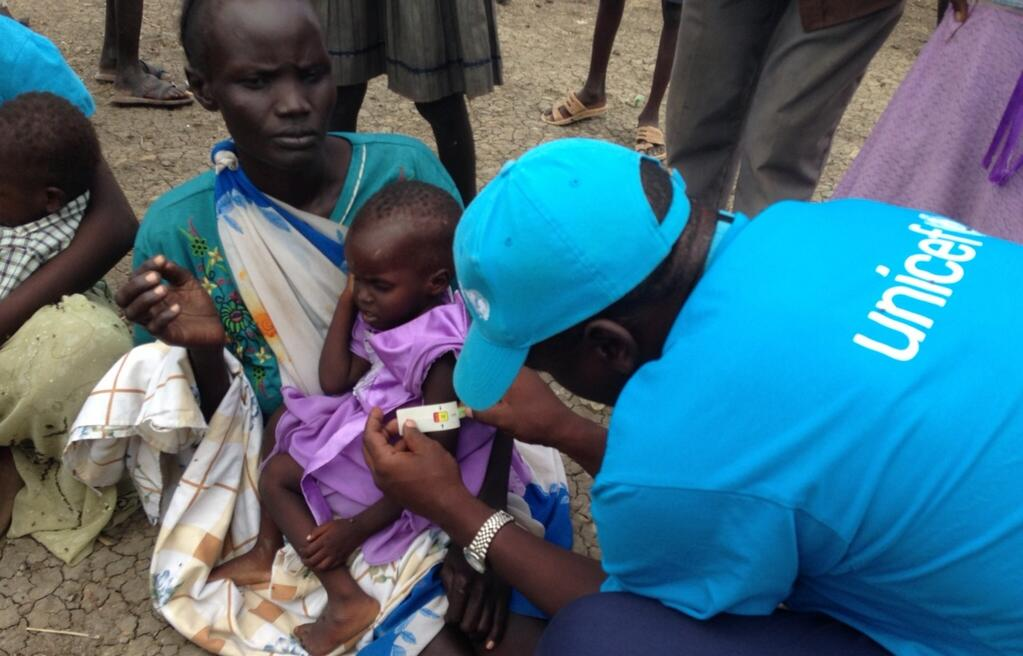 A health worker uses a MUAC arm measurement tape to screen a South Sudanese child for malnutrition.