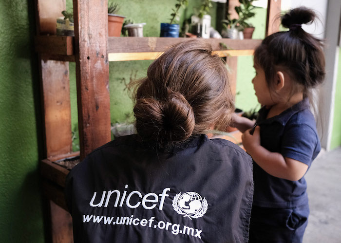 A UNICEF worker plays with a toddler at a shelter in Tijuana, where her family is waiting for their U.S. asylum application to be processed.