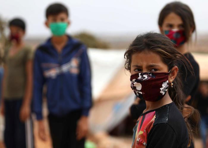 On 27 July 2020, children wear face masks sewn by displaced Syrian women at a camp for internally displaced persons near the town of Maaret Misrin in Syria's northwestern Idlib province, amidst the crisis of the COVID-19 pandemic.