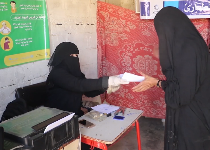 A woman receives her emergency cash transfer payment from a UNICEF-supported worker in Yemen's Sada'a region. The payment allows families to buy lifesaving essentials.