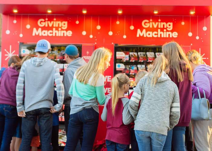 Familes gather around the Giving Machines to choose the local and global organizations they want to support this holiday season.