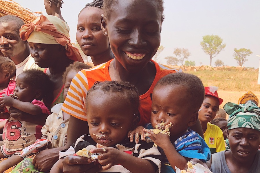 In the Central African Republic, a mother smiles as her twins feed themselves with Plumpy'Nut Ready-to-Use Therapeutic Food at a UNICEF-supported health center.