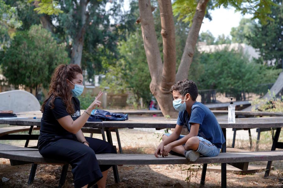 After the Beirut explosions in August 2020, 10-year-old Abdulkarim chats with a UNICEF-trained volunteer at a Child-Friendly Space set up in a municipal park in Karantina, a Beirut suburb.