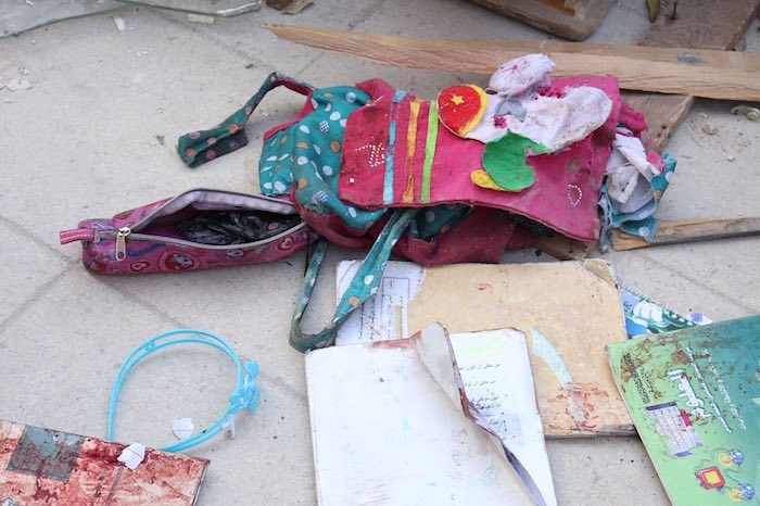 The back pack of 9-year old Zaina, and the textbook of her sister Lamar, 11. Zaina and Lama as well as Ismail, 5, and his sister Hanadi, 9, were killed by a mortar attack on their way to school in Aleppo.
