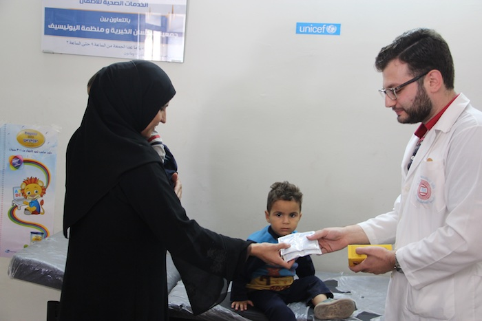 A doctor dispenses medicine to a woman holding a child at a UNICEF-supported clinic in Aleppo.