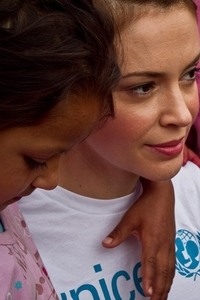 Alyssa Milano with a young child in Kosovo.