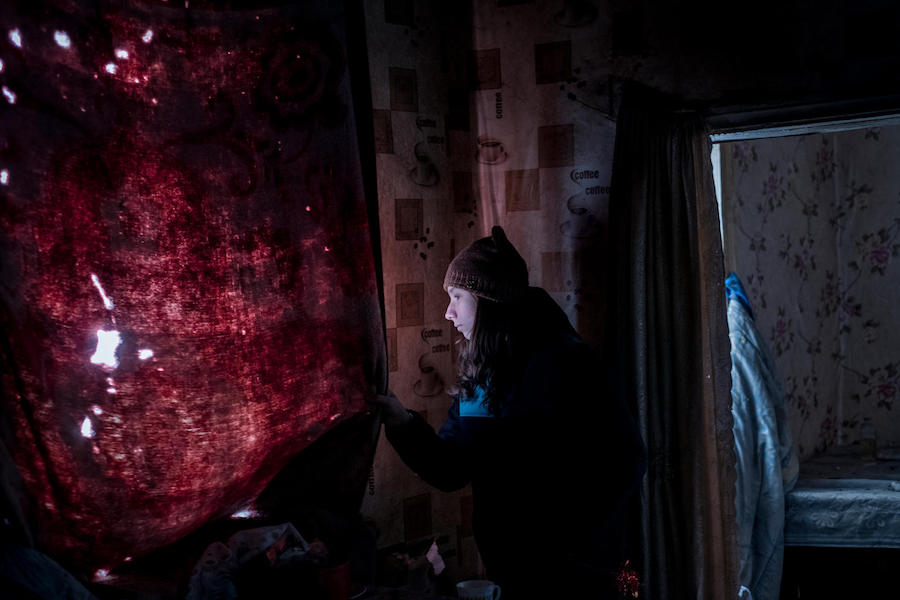 Anya, 13, looks out the window of her old, now destroyed home in Avdiivka, Donetsk Oblast, eastern Ukraine in November 2017.