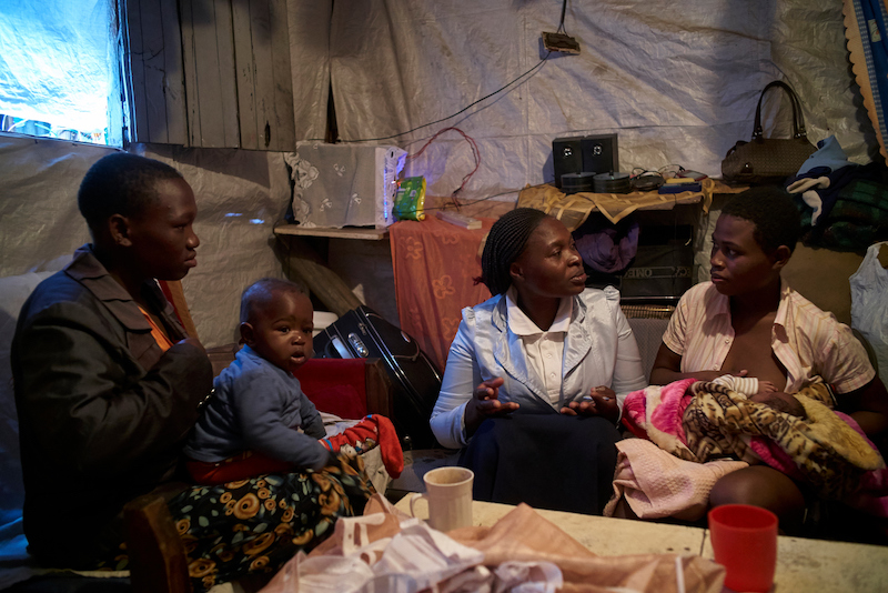 Susan Ateka (second from right), a community health worker supported by Concern, UNICEF's implementing partner, visits Maximila, 22, (right) who gave birth to her daughter Gloria two weeks ago at her home in Mukuru, Nairobi, Kenya.