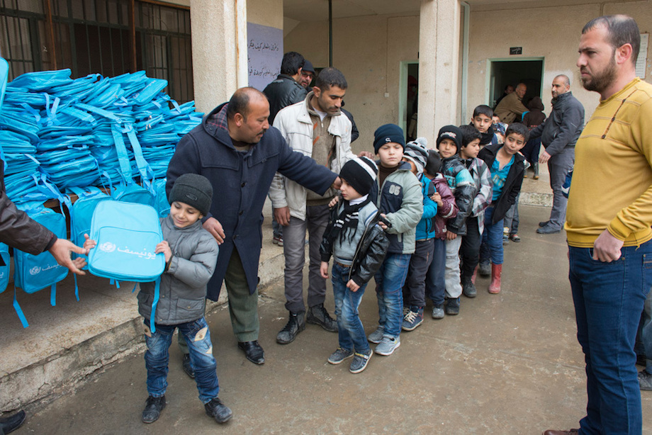 Children line up to receive backpacks supplied by UNICEF at Koofa Boys School, eastern Mosul, Iraq.