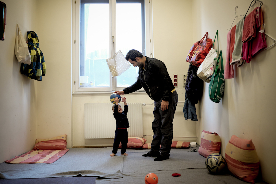 On 5 December 2015, 1-year-old Mohammad Taha Ibrahimi plays with his father, Abdul Anath Ibrahim, 32, in their room at an emergency shelter in Vienna. They are among refugees, primarily from the Syrian Arab Republic, Iraq and Afghanistan, who are living a