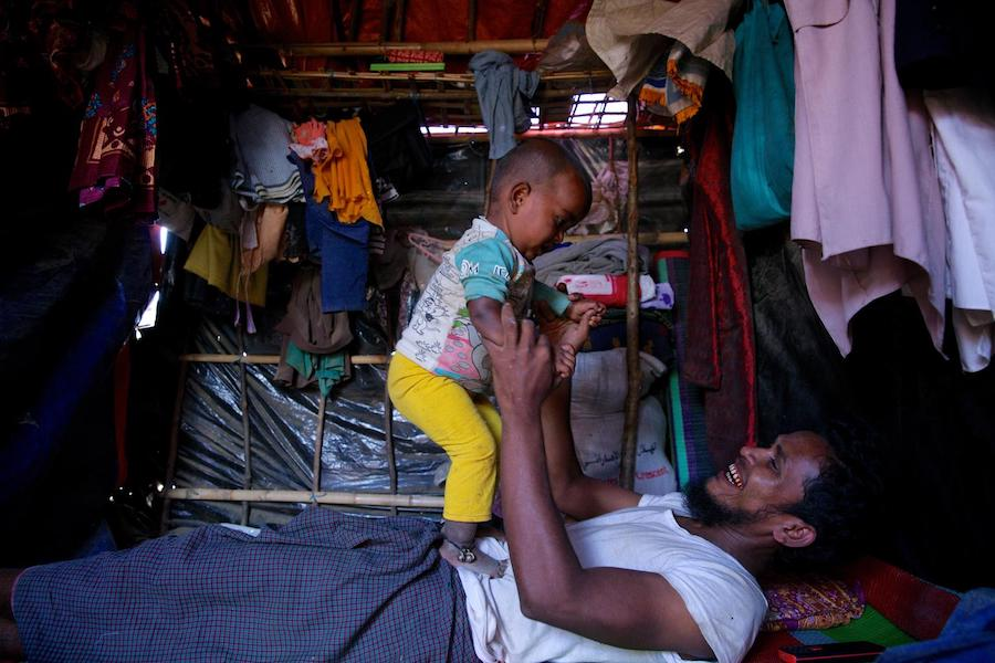 Rohingya refugee Saber, 28, plays with his 18-month-old daughter Mobashera Bibi inside their shelter in Burmapara makeshift settlement, Cox's Bazar, Bangladesh in December 2017.