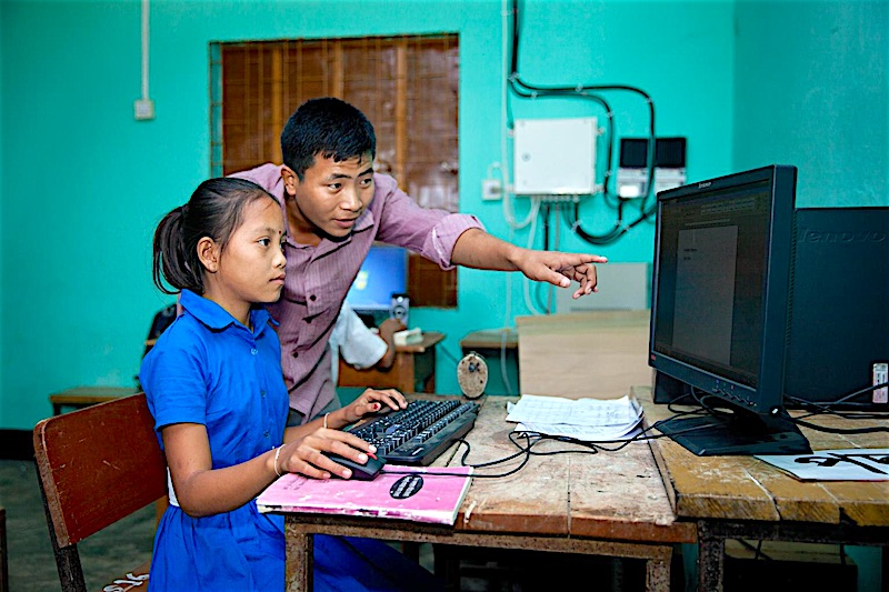 Anamika Chakma, 10 when this photo was taken, is helped by her teacher to learn how to use a computer in a UNICEF-supported Child Friendly Schools program in Bangladesh