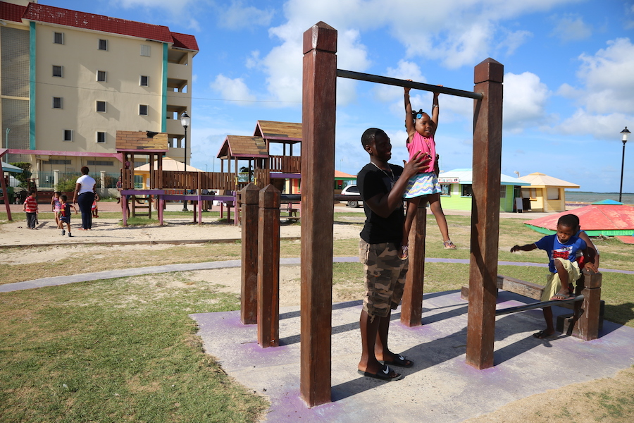 On 13 August 2016, 3-year-old Alishia (center) plays with her brother, 17-year-old Andrew, and her cousin, KJ, in a park by the water in Belize City.