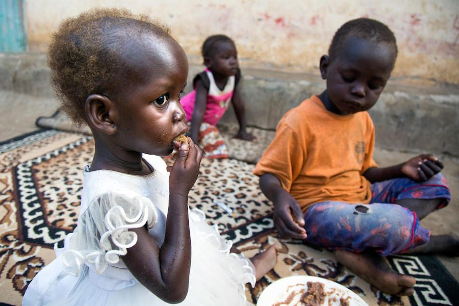 Maria, 2, and her brother Chris, 5, eat dinner at their family's home in Juba, South Sudan. Maria was treated for severe acute malnutrition at a UNICEF-supported health center in October 2017.