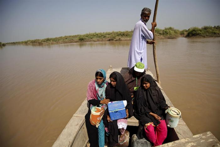 UNICEF-supported health workers cross the Indus River to a flooded village to vaccinate young children. One of them carries an insulated 'cold box' to keep vaccines at a constant low temperature to maintain their potency.