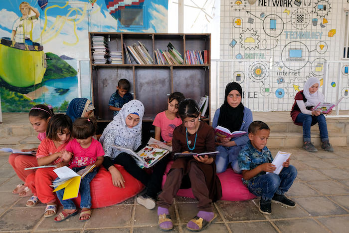On 11 September 2017, Syrian girls and boys sit and read at a UNICEF-supported center for children in Za'atari refugee camp, Mafraq Governorate, Jordan.