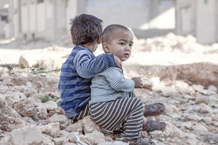Syrian Arab Republic, Esraa, 4, and her brother Waleed, 3, sit on the ground near a shelter for internally displaced persons