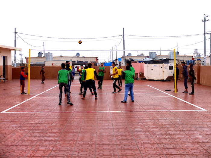 Boys play volleyball outside a series of offices for computer classes and women's vocational training, in Debaga camp in Iraq.