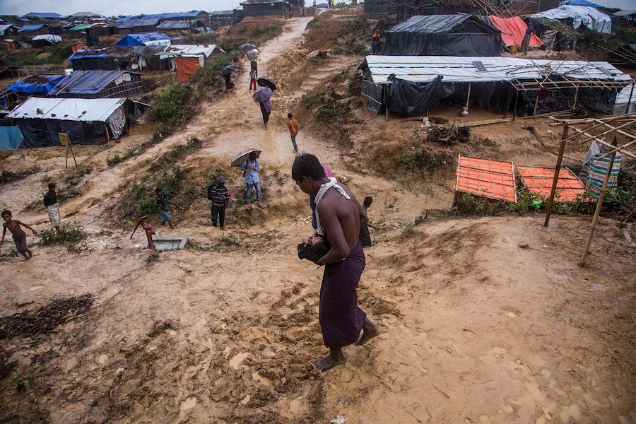 A boy carries his 4-day-old niece down a muddy slope in the sprawling Kutupalong camp for Rohingya refugees in Cox's Bazar Bangladesh in October 2017.