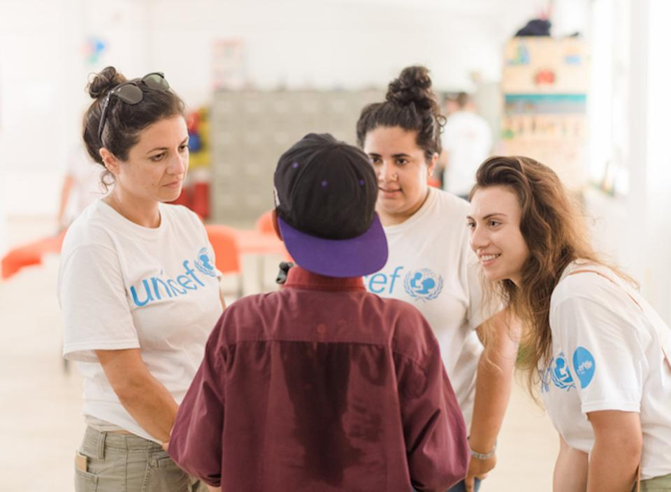 Members of UNICEF NextGen listening to an unaccompanied child migrant tell his story.