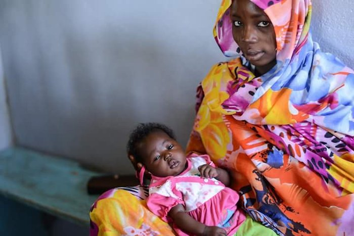 A mother and child wait to be vaccinated by UNICEF and partners in Chad in February 2016.