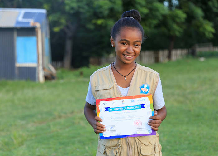 Christelle, 16, a member of the UNICEF-supporter Junior Reporters Club in Taolagnaro, Madagascar, holds her radio reporter's training certificate in 2019.