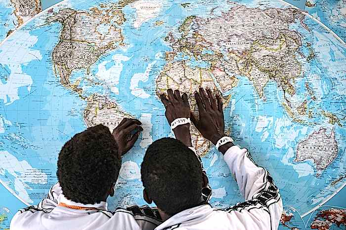 Gambian asylum seekers review their journey while looking at a map on the wall at a Hot Spot, an asylum seeker reception center in Pozzallo, Sicily, Italy.
