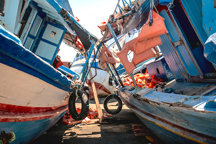 """Boats, in a """"graveyard"""" in Pozzallo, Sicily, used by Libyan smugglers to ferry refugees across the sea to Italy."""