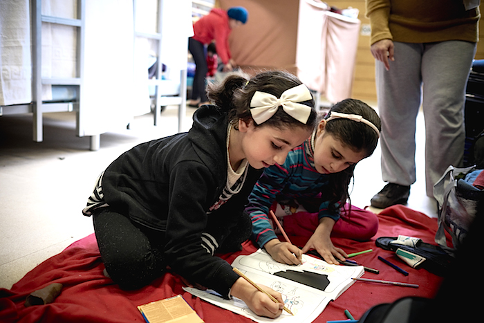 Jannat, 7, a refugee from the destroyed Syrian city of Homs, draws with other child refugees at an emergency shelter in Berlin, Germany.