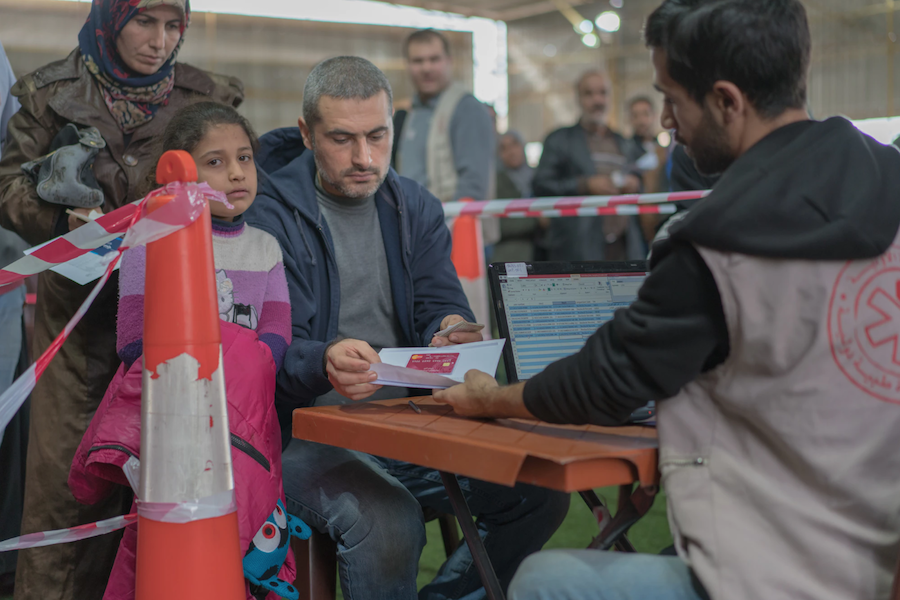 Ahmad, a Syrian refugee, in Lebanon, plans to pay for his daughter's school transportation to school using the LOUISE common card, which administers cash transfers.