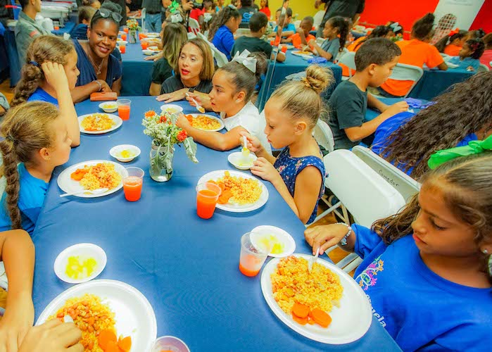 UNICEF USA's Anucha Brown (left) and Olga Ramos, President of the Boys & Girls Clubs of Puerto Rico talk with kids enjoying dinner at the Las Margaritas Club.