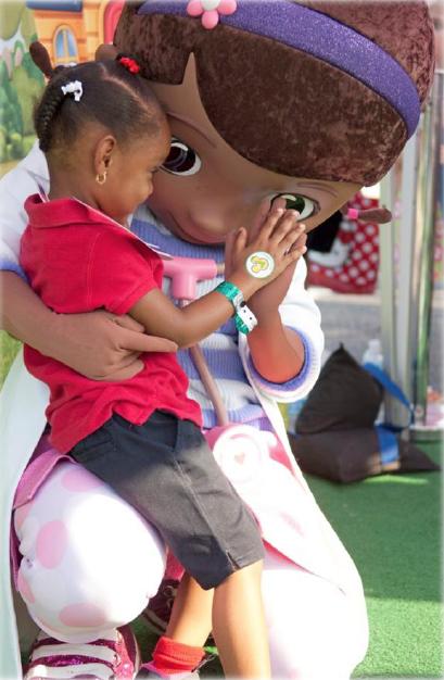 Doc McStuffins high fiving a child