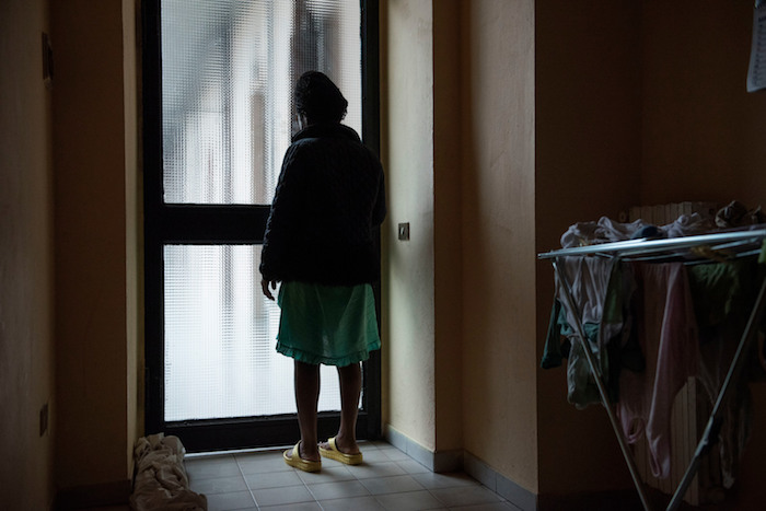 Diane, a Nigerian girl who is pregnant with twins after being forced into prostitution following her arrival in Italy via the Mediterranean Sea route from Libya, stands in a home where she is being sheltered in Asti, Italy.