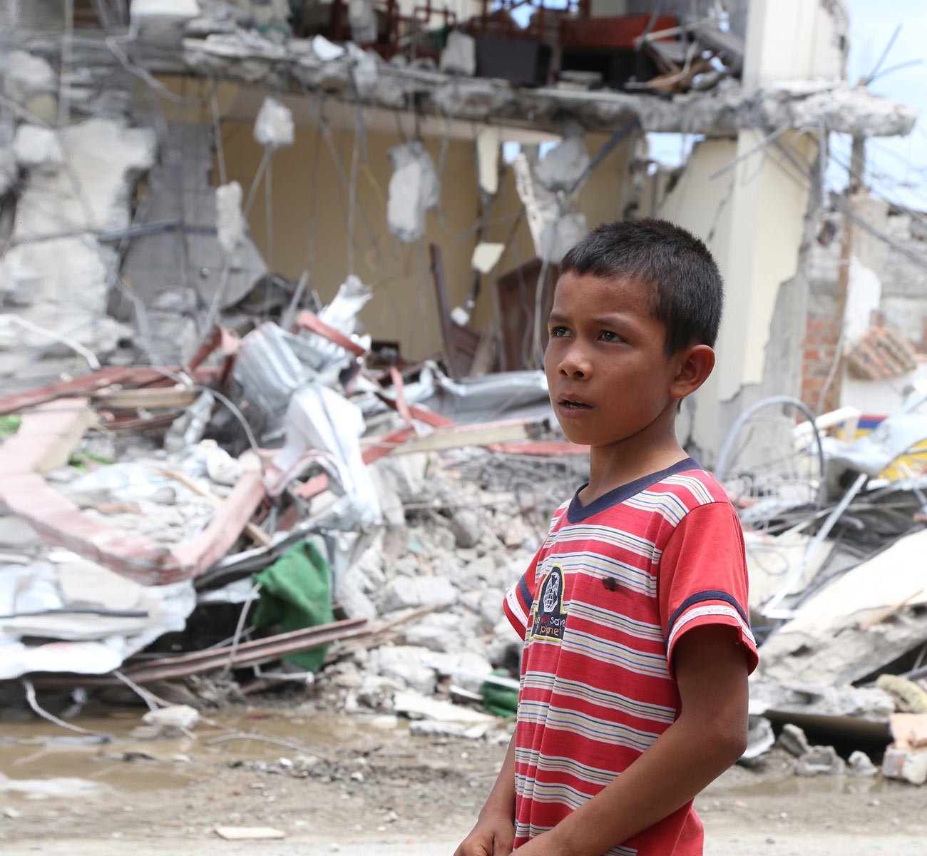 A boy contemplates the ruins of a thoroughfare in an Ecuadorian village devastated by earthquakes