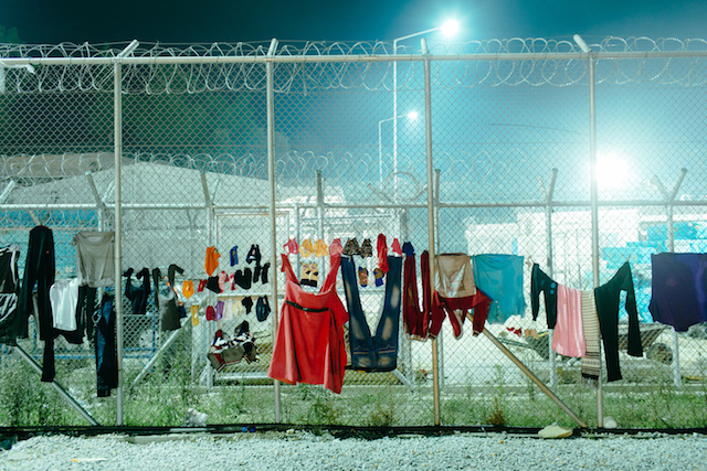 Refugees in limbo in Greece drying their clothes on a fence.
