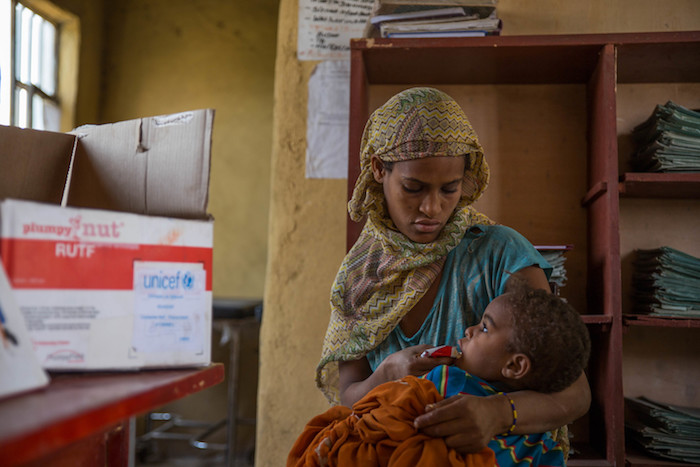 In Ethiopia, Marianna feeds 2-year-old Tamina a packet of Ready-To-Use Therapeutic Food at a UNICEF-supported health post where young children are screened for malnutrition.