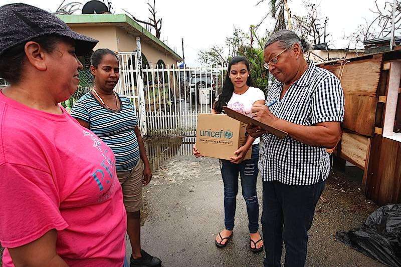 Two women deliver a UNICEF Family Dignity and Hygiene Kit to two other women in Puerto Rico to help them recover from Hurricane Maria