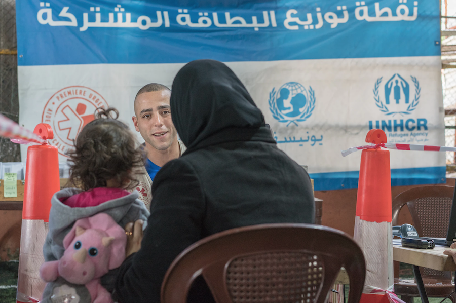 A Syrian mother and child receive their LOUISE common card from an aid worker outside Beirut, Lebanon in January 2018.