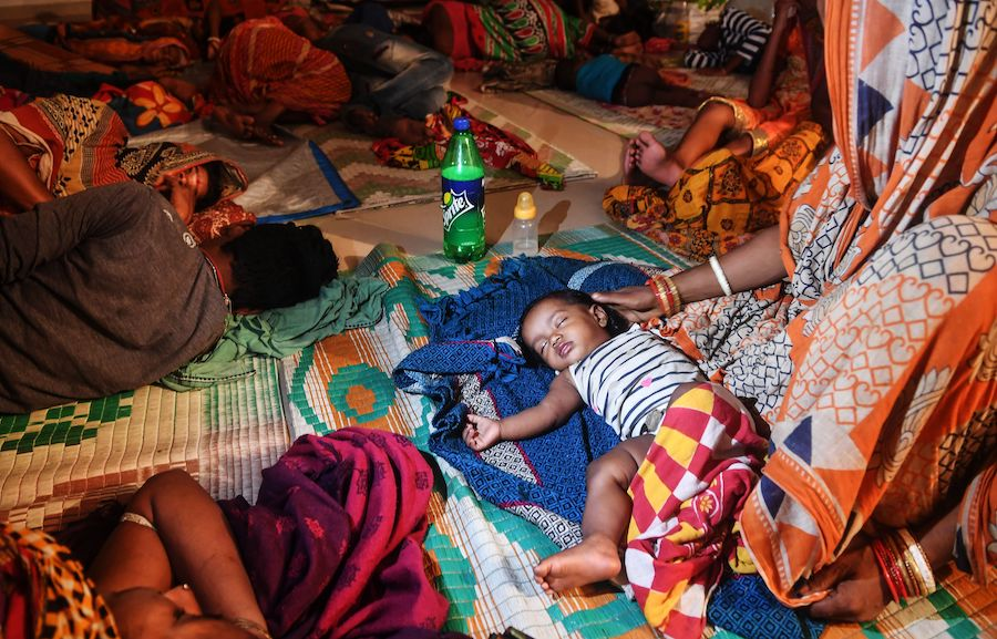 Families evacuated for safety rest at a temporary cyclone relief center in Puri in the eastern Indian state of Odisha on May 3, 2019, as Cyclone Fani approaches the Indian coastline.