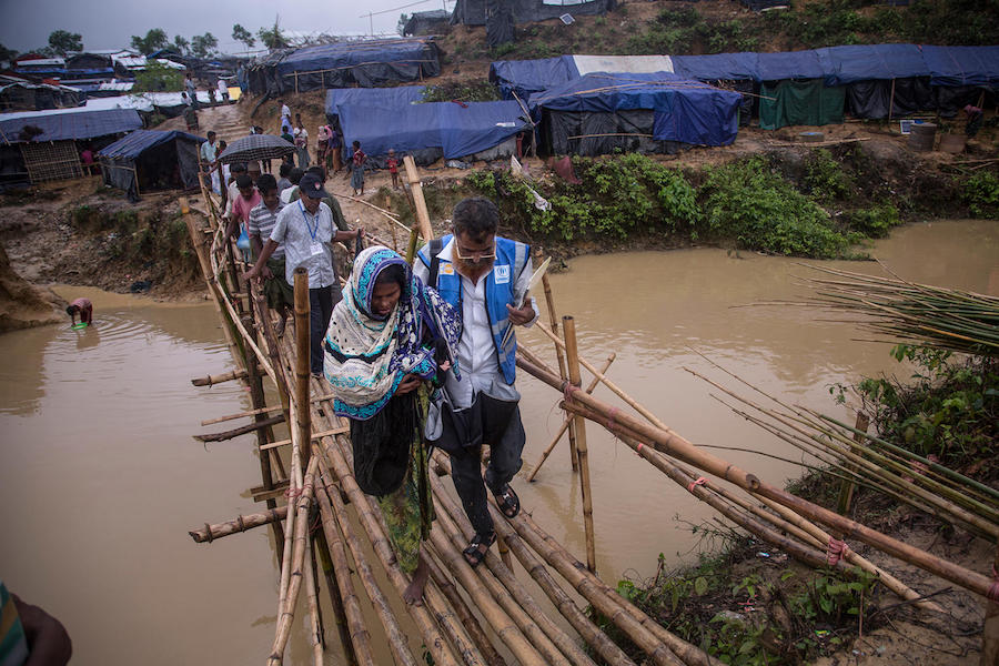 Carryin her newborn granddaughter, Johora, accompanied by a volunteer health worker, crosses a rickety bamboo bridge in the sprawling Kutupalong camp for Rohingya refugees in Cox's Bazar, Bangladesh.