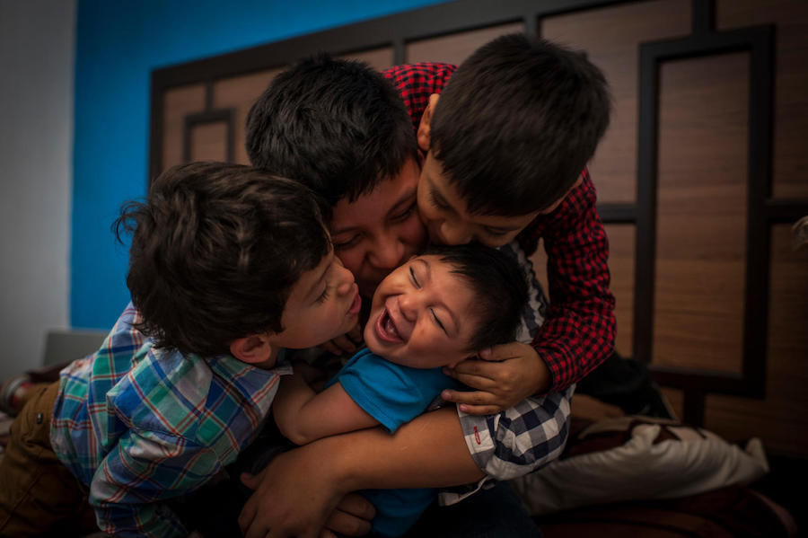Nine-month-old Danilo (in blue) laughs as his brothers shower him with kisses in their home in Guatemala City. Danilo, who has Congenital Zika Syndrome and microcephaly, gets loving care from his family and his community.