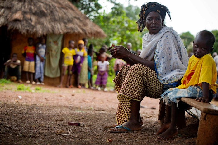 In Siguiri, Guinea, Sita sits beside her grandson, Lounceny, who contracted polio as a baby because he was not vaccinated.