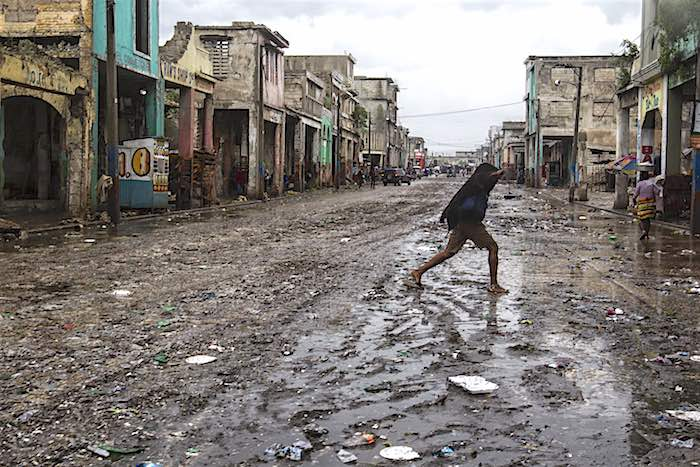 On 4 October 2016, a woman crosses the street in downtown Port au Prince after Hurricane Matthew passed over Haiti.
