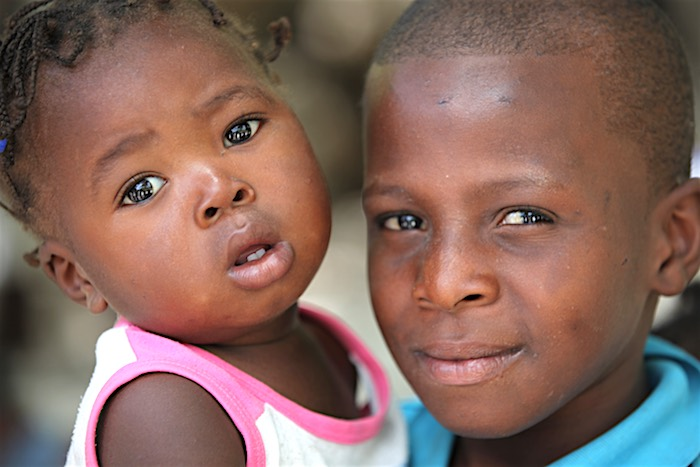 Two Haitian children at the UNICEF-supported mobile vaccination station set up outside a church by the side of the road in Thomand II.